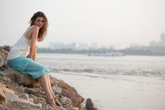 Woman sitting near water. Beautiful brunette  woman sitting on rock near water Stock Photo