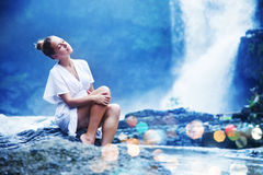 Woman sitting near waterfall Royalty Free Stock Images