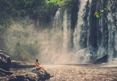 Woman sitting near waterfall enjoying the sun, Phnom Koulen at Siem Reap, Cambodia Royalty Free Stock Images