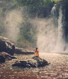 Woman sitting near waterfall enjoying the sun, Phnom Koulen at Siem Reap, Cambodia Stock Image