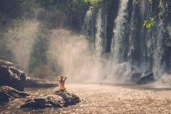 Woman sitting near waterfall enjoying the sun, Phnom Koulen at Siem Reap, Cambodia Stock Image