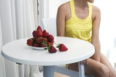 Woman sitting near the table with a plate of fresh strawberries Royalty Free Stock Photography