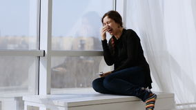Woman sitting near the window on a Sunny day and laughing stock footage