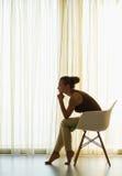 Woman sitting near window in thoughtful pose Stock Image