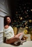 Woman sitting near winter christmas tree with gold balls decorat Royalty Free Stock Photos