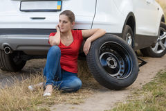Woman sitting next to the car with flat tire and waiting for hel. Young woman sitting next to the car with flat tire and waiting for help Stock Photo