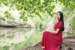 Woman sitting next to a river alone Royalty Free Stock Photos