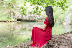 Woman sitting next to a river alone Royalty Free Stock Images