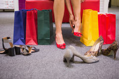 Woman sitting next to shopping bags and putting on shoes Royalty Free Stock Images