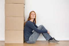 Woman Sitting Next to Storage Boxes. A young woman sitting by herself next to a tall stack of storage boxes Stock Photo