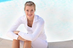 Woman sitting next to swimming pool Stock Photo