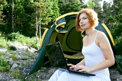 Woman sitting next to a tent with  laptop Stock Image
