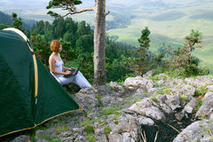 Woman sitting next to a tent with  laptop Royalty Free Stock Photo