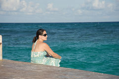 Woman sitting by the ocean Royalty Free Stock Photo