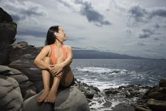 Woman sitting by ocean Royalty Free Stock Images