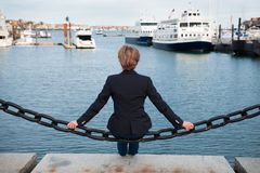 Woman sitting on ocean pier thinking and dreaming. View from the back. Royalty Free Stock Photography
