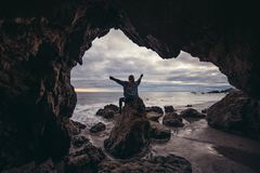 Woman sitting on the ocean rocks cave with arms raised and enjoy the nature and freedom Stock Photos