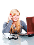 Woman sitting in office and calling by phone Stock Photography