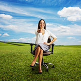 Woman sitting on the office chair. Laughing woman sitting on the office chair and pointing at camera. photo on the green meadow over blue sky Stock Images
