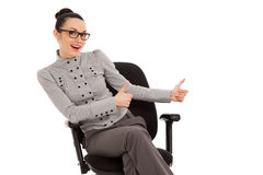Woman sitting in office chair presenting something Royalty Free Stock Photos
