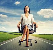 Woman sitting in the office chair on road Royalty Free Stock Image