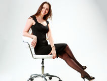Woman sitting on the office chair. Smiling woman sitting on the office chair and looking away over gray background Stock Photos