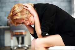 Woman sitting on the office chair touching her head Royalty Free Stock Image