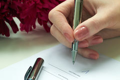 Woman  sitting at office desk signing a contract Royalty Free Stock Photo