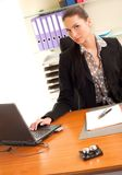 Woman sitting in the office in front of the laptop. Business woman sitting in the office in front of the laptop Royalty Free Stock Photography