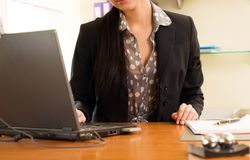 Woman sitting in the office in front of the laptop Stock Image