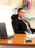 Woman sitting in the office in front of the laptop. Business woman sitting in the office in front of the laptop Royalty Free Stock Photos