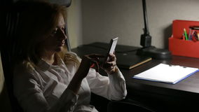 Woman sitting in the office at the table and wrote messages on the smartphone. stock footage