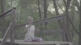 Woman sitting on the old bridge with singing bowl. Attractive woman sitting on the old bridge in a park with singing bowl in her hands. Gold time shooting stock video footage