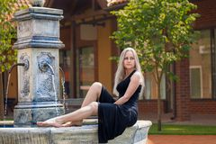 Woman sitting on the old drinking fountain barefoot Royalty Free Stock Photo