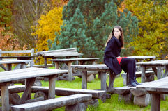 Woman sitting on old park cafe wooden table in. Picture of young woman in coat sitting on wooden table in old park cafe. Charming girl with long hair waiting for Stock Photos