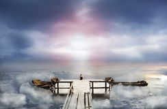 Woman sitting on an old pier in the sky Stock Photography