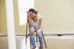 Woman Sitting On Ladder In Empty Space Looks Tired Royalty Free Stock Photography