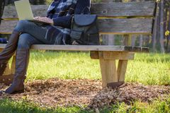 Woman Sitting On Park Bench With Laptop Computer Stock Photos