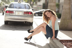 Woman Sitting On The Curb Smiling Stock Images