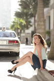 Woman Sitting On The Curb Smiling Royalty Free Stock Photos