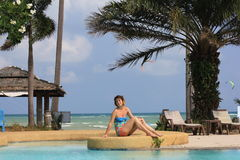 Woman sitting at open-air swimming pool among palm Stock Photo