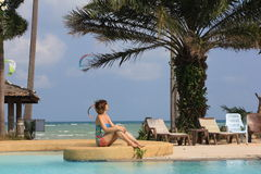Woman sitting at open-air swimming pool among palm Royalty Free Stock Photos