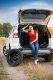 Young woman sitting in open car trunk waiting for auto service to change flat tire. Woman sitting in open car trunk waiting for auto service to change flat tire Royalty Free Stock Photos