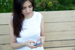 Woman sitting on the outdoor bench Stock Photography