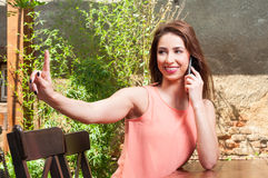 Woman sitting outdoor ordering and talking on phone Royalty Free Stock Photo