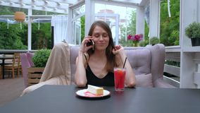 Woman sitting In outdoor Restaurant talking mobile phone. Pretty brunette woman sitting In outdoor Restaurant and talking her mobile phone stock footage