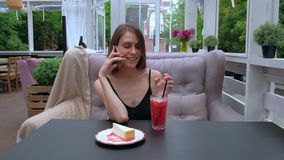 Woman sitting In outdoor Restaurant talking mobile phone. Tilt Left - Beautiful woman in a good mood, drinking a strawberry smoothie cheesecake in Restaurant stock footage