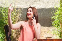 Woman sitting outdoor talking at phone and ordering Royalty Free Stock Image