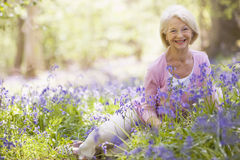 Woman sitting outdoors with flowers smiling. At camera Royalty Free Stock Photo