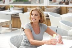 Woman sitting outdoors with a glass of water Stock Photo